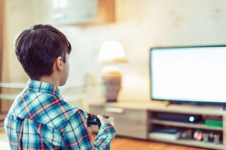 Young boy playing video game by controller on console empty space