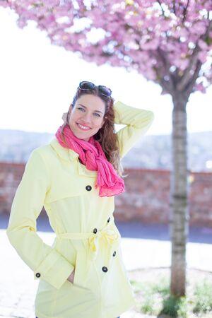 Young redhead woman in pink scarf walking in park during springtime Sakura