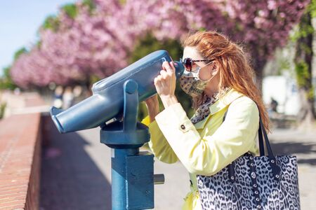 Young redhead tourist woman watching into binoculars in park at springtime