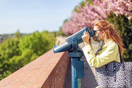 Young redhead tourist woman watching into binoculars in park at springtime during pandemic