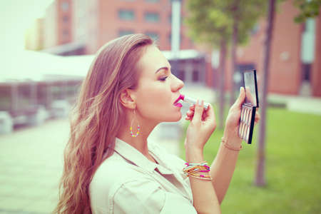 Young Latina woman applying lipstick before dating outdoors