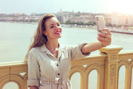 Young brunette woman tourist taking selfie on bridge while sightseeing Stockfoto - 151084435