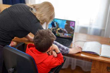 Mother turning off computer for computer addicted little gamer kid, internet and game dependency