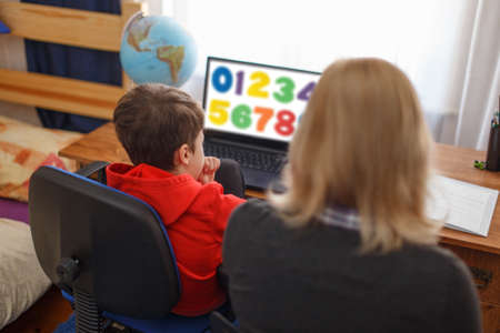Mom helps learning maths on laptop to son at home