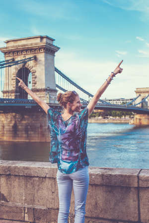 Young redhead woman with arms raised and looking away at Chain Bridge, Budapest, Hungary 免版税图像