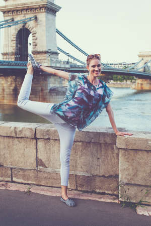 Young carefree woman with toothy smile doing swan yoga pose at Budapest, Hungary
