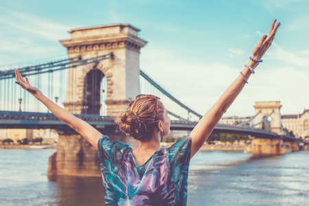 Thankful young redhead woman with arms raised at Chain Bridge, Budapest, Hungary