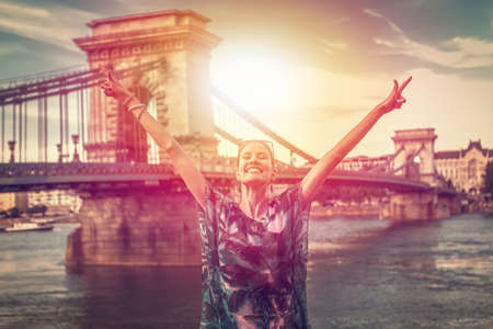 Successful winner urban woman with arms raised at Budapest, Hungary