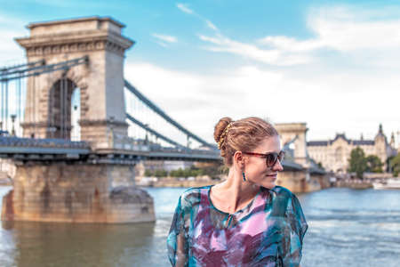 Happy young redhead woman looking away at Chain Bridge, Budapest, Hungary 免版税图像