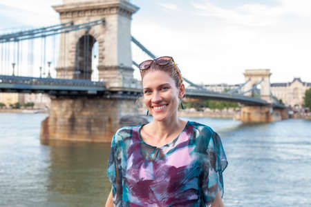 Happy young positive woman with toothy smile posing at Chain Bridge, Budapest, Hungary