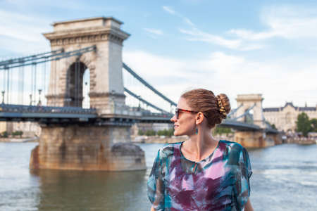 Happy young Caucasian woman looking away at Chain Bridge, Budapest, Hungary