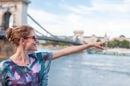 Redhead woman pointing to Chain Bridge at Budapest, Hungary