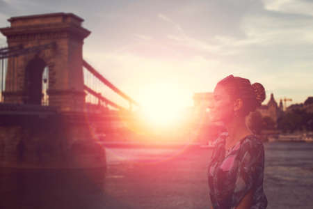 Young woman daydreaming in sunrise at Szechenyi Chain Bridge at Budapest, Hungary