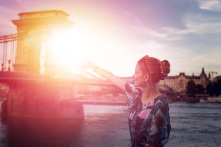 Young redhead woman pointing to Chain Bridge at Budapest in sunrise, Hungary