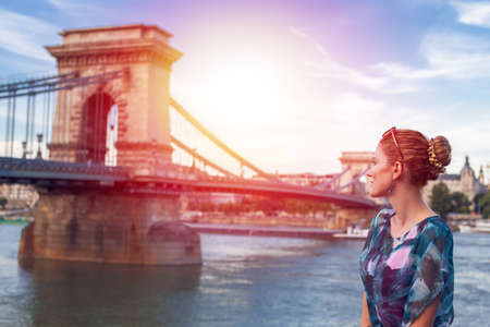 Young woman posing at Szechenyi Chain Bridge in Budapest with light of hope, Hungary