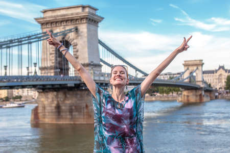 Happy young woman with arms raised at Chain Bridge, eyes closed, Budapest, Hungary