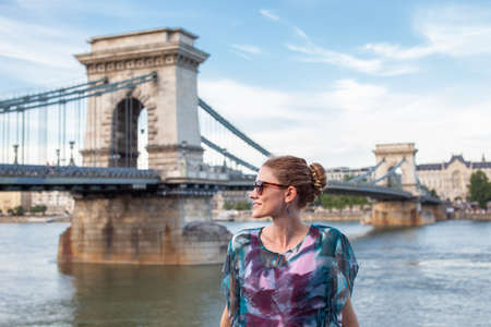 Happy young traveler woman looking away at Chain Bridge, Budapest, Hungary 免版税图像