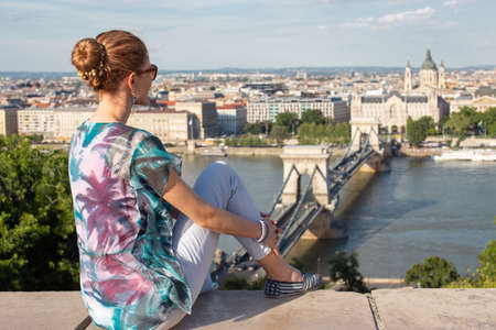 Young redhead Caucasian 20s woman sitting in Budapest panorama, Hungary