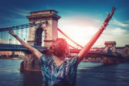 Beautiful grateful and thankful young urban woman with arms raised in sunrise at city. Travel destinations in Europe, Budapest, Hungary 免版税图像