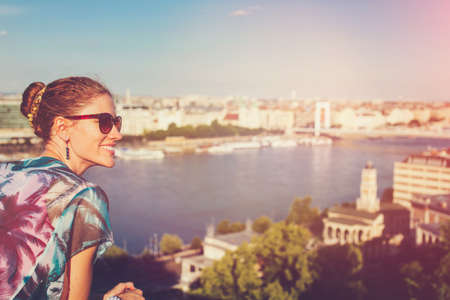 Young positive urban woman wondering in city panorama Budapest, Hungary 免版税图像