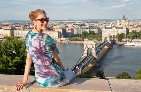 Happy young redhead Caucasian 20s woman sitting and toothy smile at Budapest panorama, Hungary
