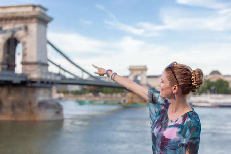 Young 20s redhead woman pointing to Chain Bridge at Budapest, Hungary