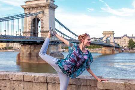 Young redhead woman doing yoga at Danube in city, swan pose, Budapest, Hungary