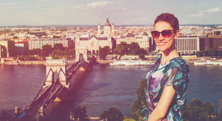 Happy young redhead Caucasian 20s woman with toothy smile at Budapest panorama, cinematic style, Hungary