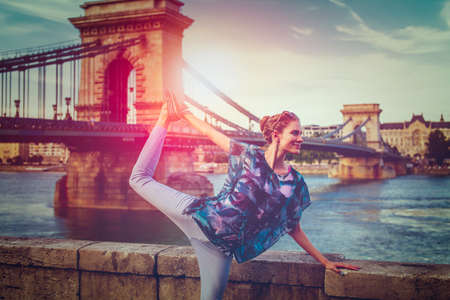 Young redhead woman doing yoga at Danube in city light, swan pose, Budapest, Hungary
