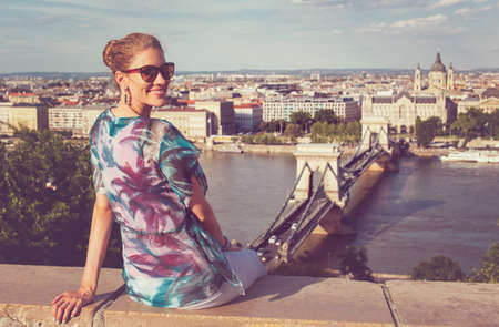 Happy young redhead Caucasian 20s woman toothy smiling while sitting at Budapest panorama, Hungary