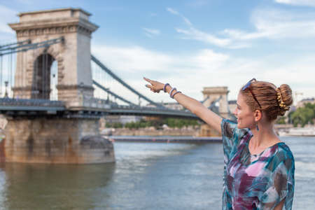 Tourist redhead woman pointing to Chain Bridge at Budapest, Hungary