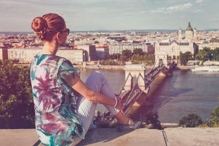 Young woman sitting in Budapest panorama, rear view, Hungary