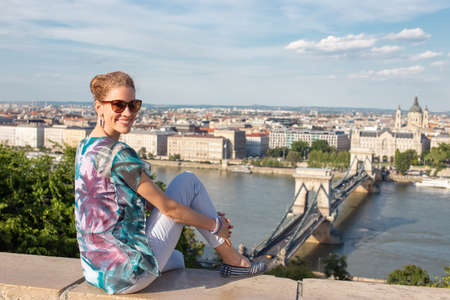 Happy young redhead Caucasian 20s woman in sunglasses toothy smile at Budapest panorama, Hungary 免版税图像