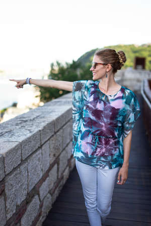 Young woman pointing into distance while sightseeing at famous place
