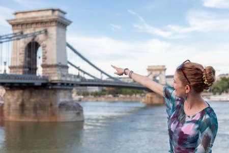Young woman pointing to Szechenyi Chain Bridge, Budapest, Hungary 免版税图像