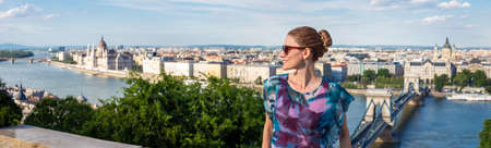 Happy young positive adult woman wondering in Budapest panorama, Hungary 免版税图像