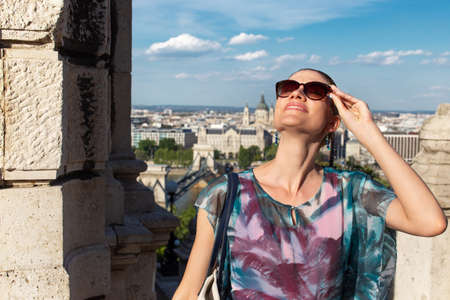 Young woman tourist looking up to the sky while sightseeing Budapest, Hungary 免版税图像