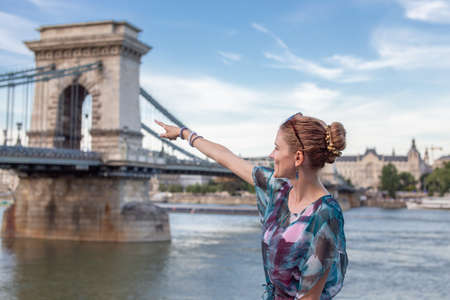 Happy young redhead woman pointing to Chain Bridge at Budapest, Hungary