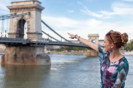 Young redhead woman pointing to Szechenyi Chain Bridge at Budapest, Hungary 免版税图像
