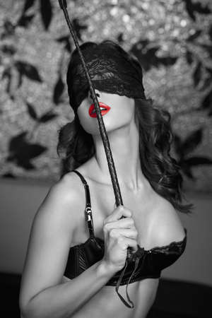 Sexy woman in lace eye blindfold holding whip black and white with red lips, bdsm