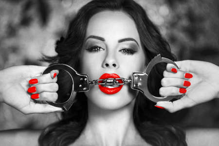 Sexy woman in latex bra holding handcuffs in bedroom in dark at night club, black and white selective coloring with red,