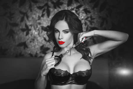 Sexy woman in latex bra holding handcuffs in bedroom in dark at night club, black and white selective coloring with red, bdsm