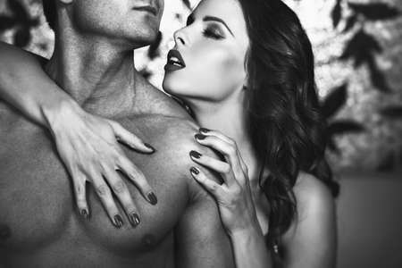 Sensual lustful woman embrace sexy man body at night, lovers, black and white