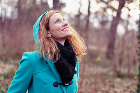 Happy young redhead Caucasian woman waiting for spring in nature, outdoors Standard-Bild