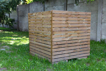 Wooden box from parallel slats at backyard, covering, hiding object