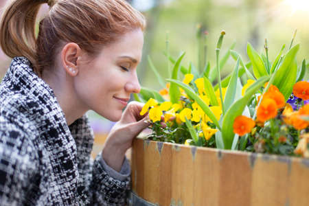 Young Casucasian woman smelling flowers at spring in public park, profile view, outdoors 版權商用圖片
