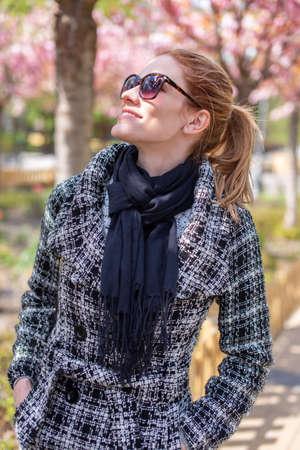 Young positive Caucasian woman toothy smiling into camera at public park during springtime Sakura 版權商用圖片