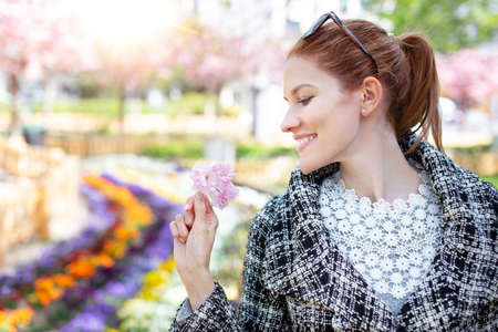 Happy young redhead Caucasian woman holding pink cherry blossom portrait