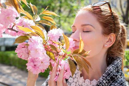 Young Caucasian redhead woman smelling cherry tree blossom, eyes closed 版權商用圖片