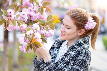 Young Caucasian redhead woman holding cherry tree blossom portrait 版權商用圖片